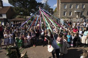 Photo of a crowd joining in to dance round the Maypole at the Mayfield Mayfair